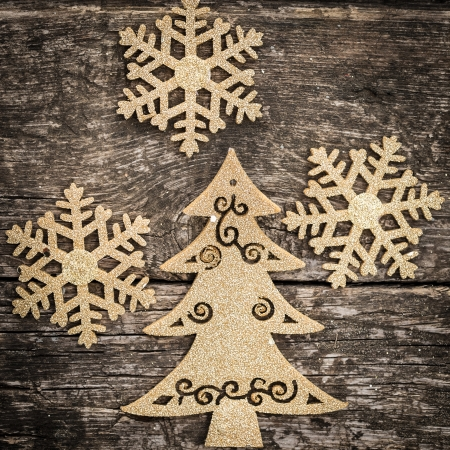 Gold Christmas tree decorations on grunge wood background  Winter holidays concept photo