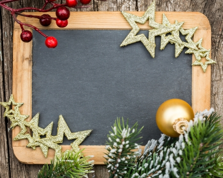Vintage wooden blackboard blank framed in Christmas tree branch and decorations  Winter holidays concept  Copy space for your text photo