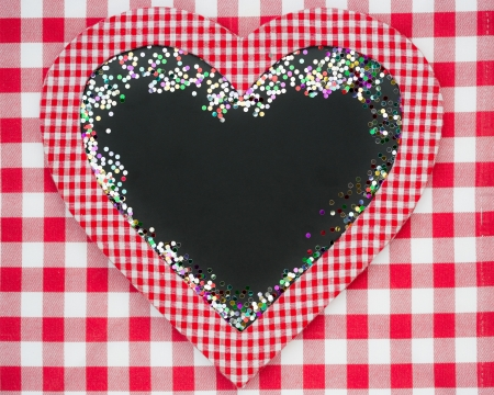 Card blank in heart shape with confetti on red gingham tablecloth  Winter holidays concept  Copy space for your text photo