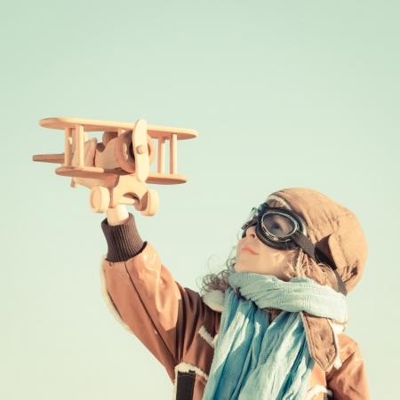 Criança feliz, brincando com o avião de brinquedo de madeira no outono Foto de archivo