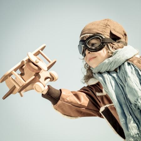 Niño feliz jugando con avión de juguete de madera en el otoño