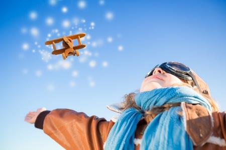 pilotos aviadores: Niño feliz jugando con avión de juguete contra el fondo del cielo azul de invierno Foto de archivo