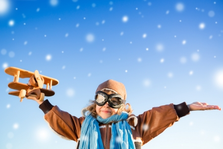Happy kid playing with toy airplane against blue winter sky background photo