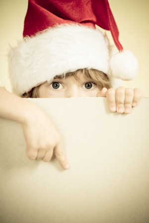 Child dressed in Santa Claus with paper blank. Christmas holidays concept. Copy space for your text. Retro toned image photo