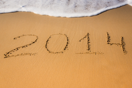 New Year 2014 is coming concept - text '2014' on a beach sand and sea wave photo