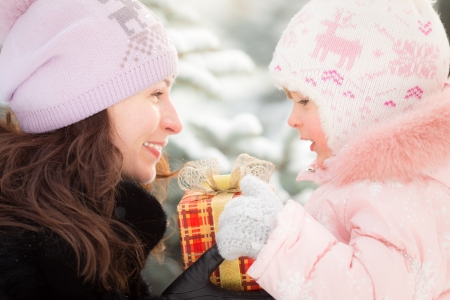 Happy family holding gift box in winter outdoors. Christmas holidays concept Stock Photo - 22737389