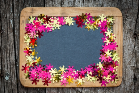 Christmas frame of confetti on vintage blackboard blank. Winter holidays concept photo