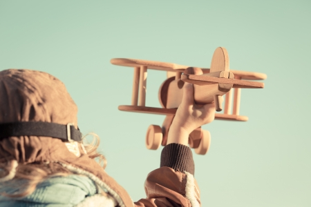 piloto: Vista posterior de ni�o jugando con avi�n de juguete de madera en el oto�o. Poca profundidad de campo