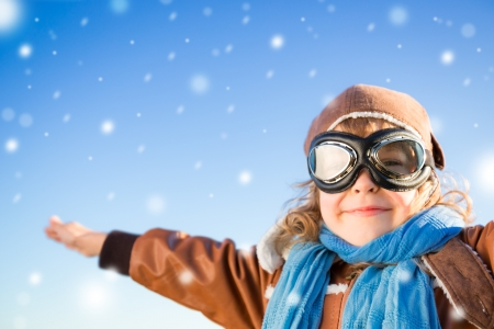 babies playing: Happy kid in the role of pilot against blue winter sky background Stock Photo
