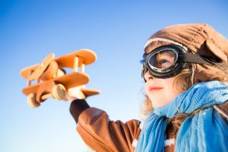 piloto de avion: Ni�o feliz jugando con avi�n de juguete contra el cielo azul de fondo Foto de archivo