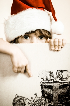 Kid dressed in Santa Claus with paper blank. Christmas holidays concept photo