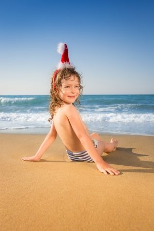Happy child in Santa hat having fun at the tropical beach. Christmas holidays concept photo
