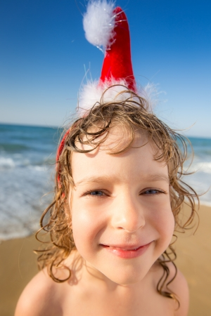 Funny closeup portrait of baby in Santa hat. Child having fun at the tropical beach. Xmas holidays concept photo