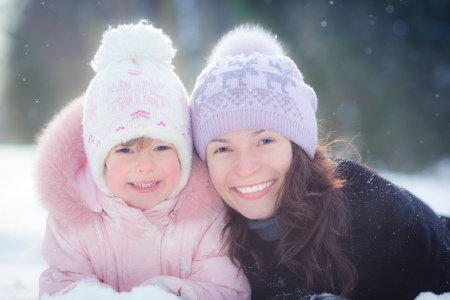 Happy family lying on snow in winter park photo