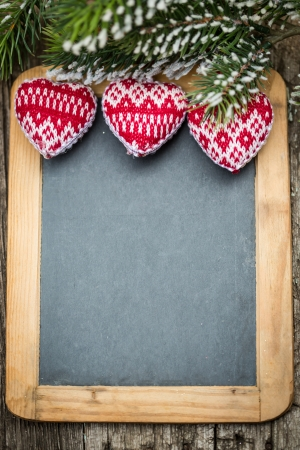 Christmas tree decorations border on vintage wooden blackboard  Winter holidays concept  Copy space for your text