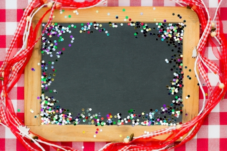 Vintage wooden blackboard with confetti on red gingham tablecloth  Winter holidays concept  Copy space for your text photo
