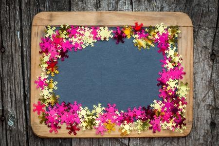 Christmas frame of confetti on vintage blackboard blank  Winter holidays concept photo