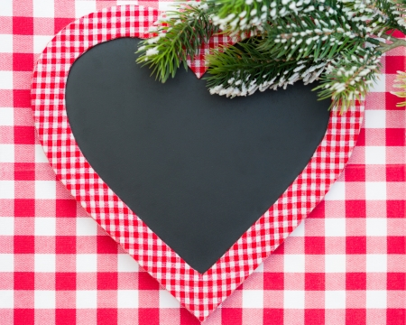 Card blank in heart shape with branch of Christmas tree on red gingham tablecloth. Winter holidays concept photo