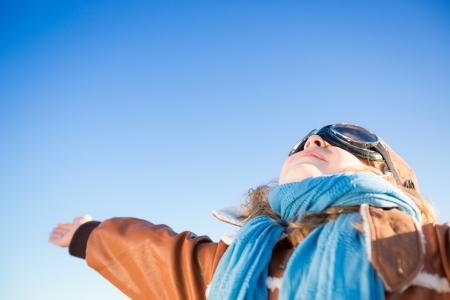 piloto: Ni�o feliz jugando con avi�n de juguete contra el fondo del cielo azul. Copie el espacio para el texto
