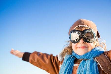 pilot: Happy kid in the role of pilot against blue winter sky background Stock Photo