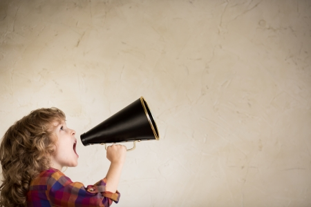 Kid schreeuwen door vintage megafoon. Communicatie concept. Stockfoto