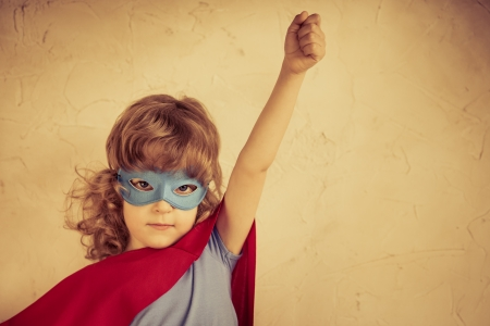 Superhero kid against grunge concrete background photo
