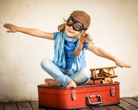 おもちゃの飛行機で遊んで喜んでいる子供