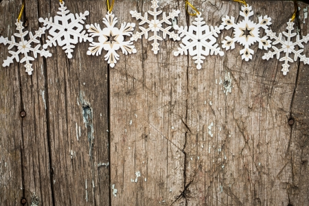 Snowflakes border on grunge wooden background  Winter holidays concept photo