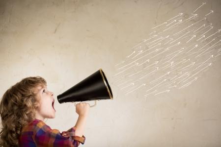 loudspeakers: Kid shouting through vintage megaphone. Communication concept.