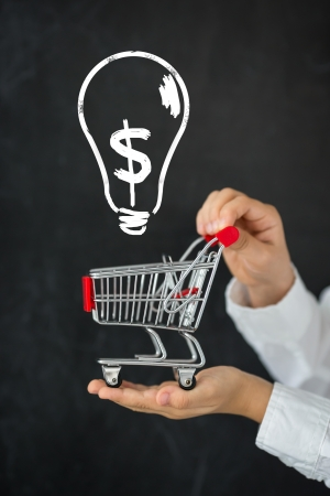 Shopping cart in hands against blackboard with drawing bulb lamp Stock Photo - 23379241