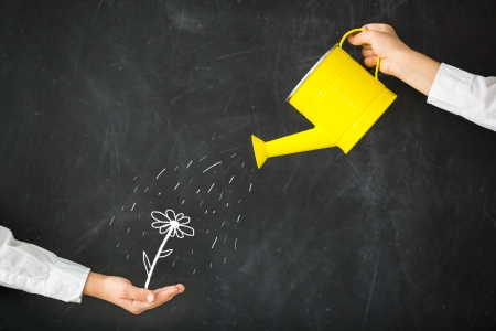 watering can: Watering can in hand against blackboard