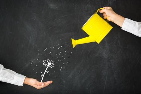 Watering can in hand against blackboard