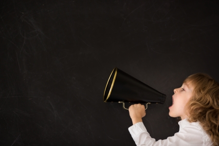 shout: Kid shouting through vintage megaphone against blackboard Stock Photo