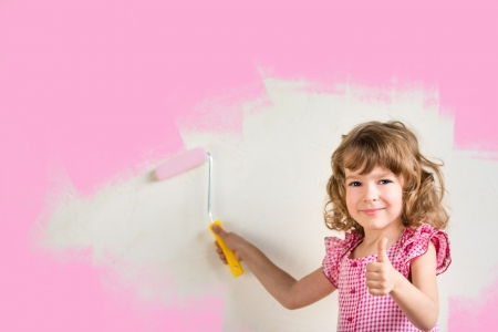 Kid painting wall with pink color. Renovation concept photo