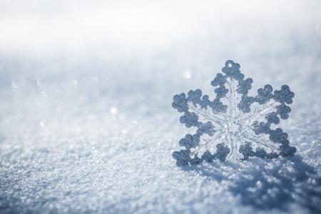 クリスマスの飾りを銀します。美しいスノーフレーク屋外本物の雪で。冬の休日の概念