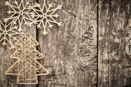 gold snowflakes: Gold Christmas tree decorations on grunge wood background. Winter holidays concept. Copy space for your text Stock Photo