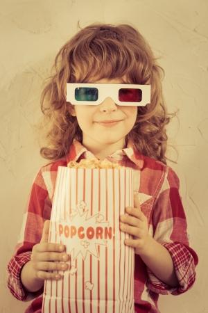 Kid mantenere il popcorn in mano. Concetto di cinema. Stile retrò Archivio Fotografico - 23431542