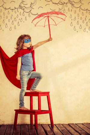 Full length portrait of superhero kid against grunge wall background photo