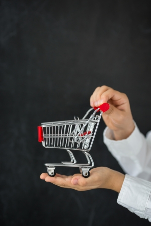 hand baskets: Shopping cart in hands against blackboard blank Stock Photo