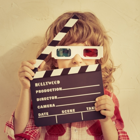 baby girl playing: Kid holding clapper board in hands. Cinema concept. Retro style Stock Photo