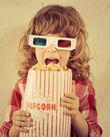 Kid holding popcorn in hands. Cinema concept. Retro style photo