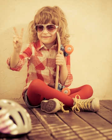 Hipster kid holding skateboard in hands photo