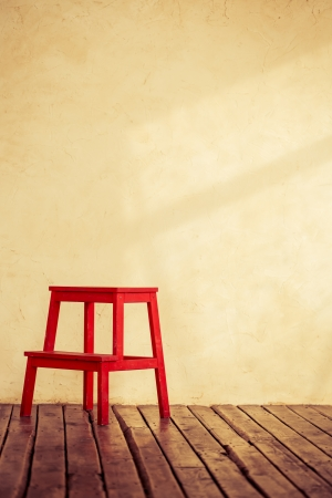 Red chair in empty room interior with grunge concrete wall and wooden floor Stock Photo - 23430768
