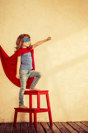 Full length portrait of superhero kid against grunge wall background Stock Photo