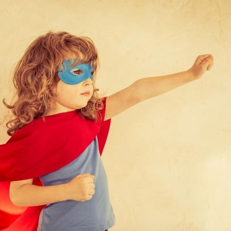superhero: Superhero kid against grunge wall background