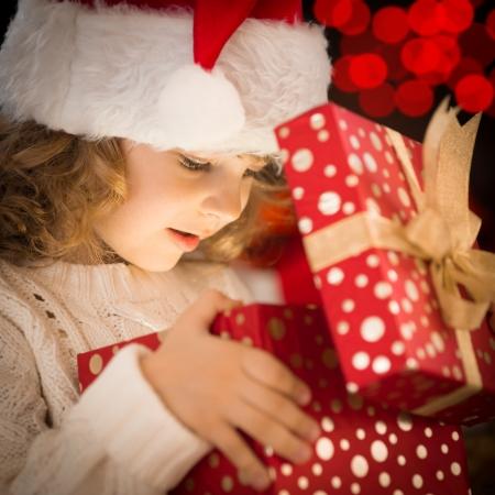 baby kerst: Gelukkig kind in de hoed van het openen kerstcadeau doos