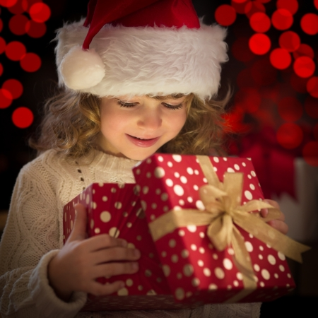 god box: Happy child in Santa hat opening Christmas gift box