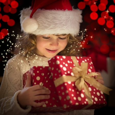 lights on: Happy child in Santa hat opening Christmas gift box