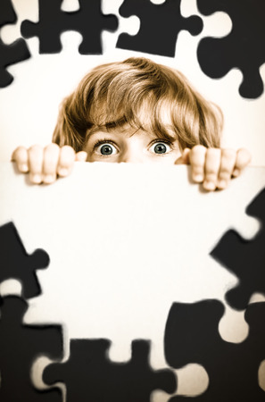 Child looking from behind the paper blank. Creative concept photo