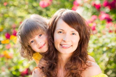 Woman and child with bouquet of flowers against green background. Spring family holiday concept. Mother`s day photo